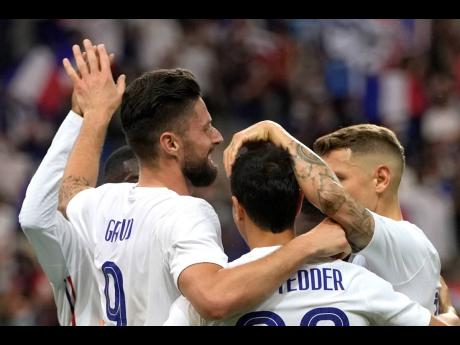 France's Olivier Giroud (left) celebrates with his teammates after scoring against Bulgaria during the international friendly football match at the Stade De France in Saint Denis, North of Paris, France, yesterday.