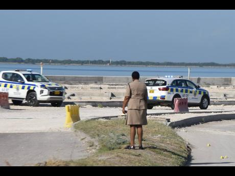 Police investigate the shooting incident near the Rae Town Fishing Village in Kingston on Wednesday. It is reported that four persons were shot by unknown assailants.