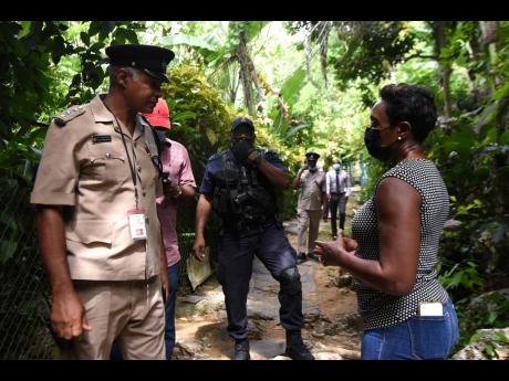 Member of Parliament for St Andrew West Rural, Juliet Cuthbert-Flynn, speaks with Deputy Superintendent of Police Collin Millaneise.