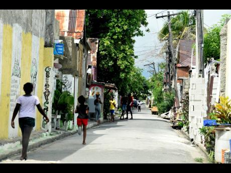 Children playing along streets of downtown Kingston on Monday even though online classes were in session.